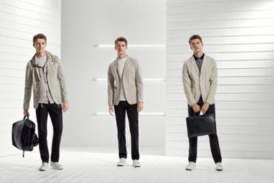 Männliches Model mit Casual-Outfit aus naturfarbenem Anzug, schwarzer Hose und weißen Sneakers von BOSS