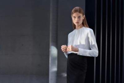 Woman is wearing a blouse and a skirt from BOSS womenswear Essential collection