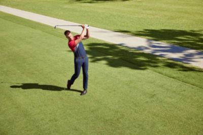 Martin Kaymer is wearing white trousers and a black polo from BOSS
