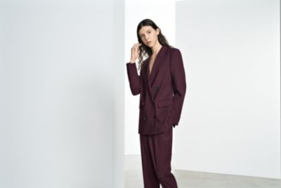 Woman is wearing dark red Fabuna knitwear and dark red Trima trousers from BOSS