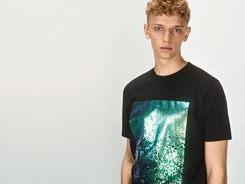 ... Le mannequin porte un t-shirt noir orné d un imprimé graphique vert HUGO 6236c9f643a1
