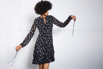 Female model wearing a black short dress with white dots from HUGO Womenswear