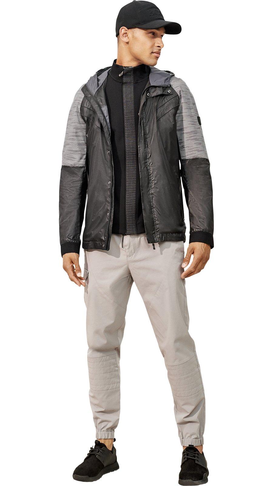 Man in black and grey outerwear, black sweatshirt, grey pants, and black  sneakers ... 7fec53892ae