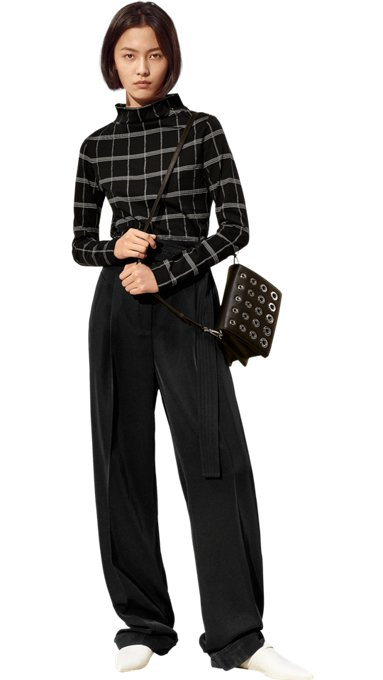 Woman in black and white top, black trousers, black bag, and white shoes ...