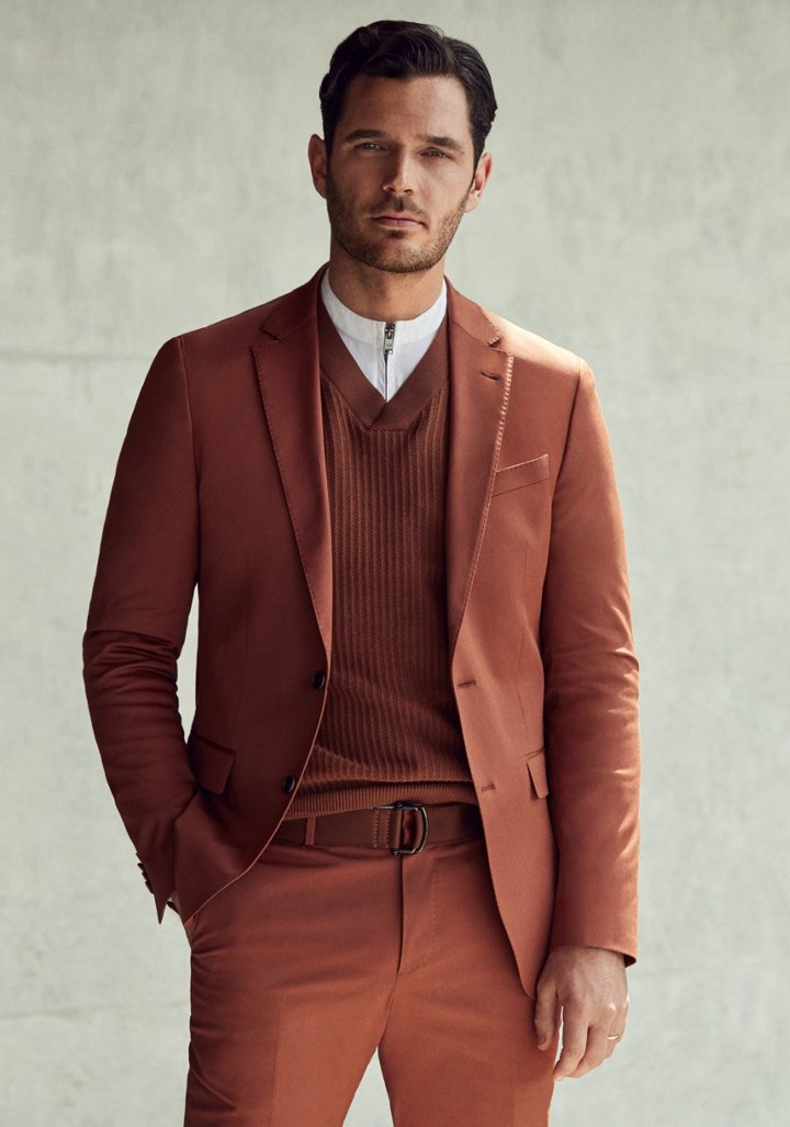 29f61a5ca94 Man is wearing a brown suit