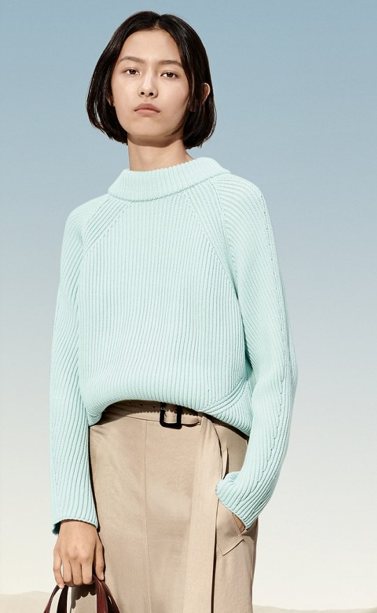28c35ee722 Woman is wearing a light blue Fonatella knitwear together with a Vayada  skirt