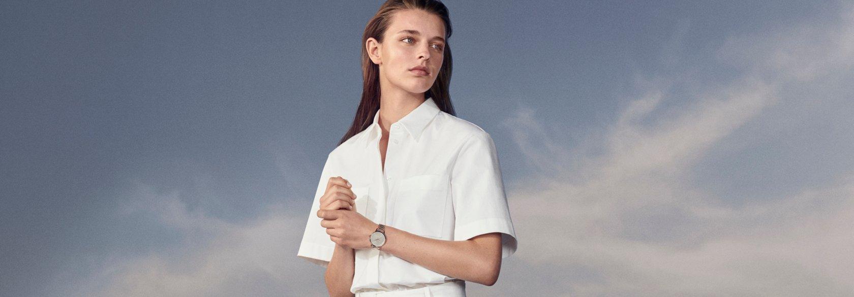 cc5b4dede3 Mujer con blusa blanca junto con pantalones blancos y reloj de BOSS ...