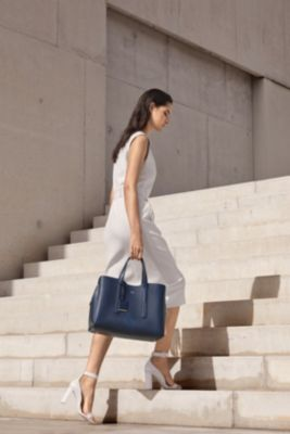 Woman is wearing a white Dadoria dress together with a dark blue Taylor tote bag and white Linda skinny heels from BOSS