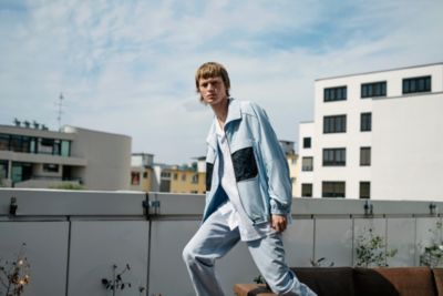 Jonas wearing a blue jacket, white shirt and blue trousers by HUGO