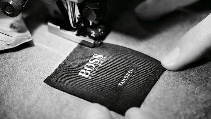 Les étapes de fabrication du costume BOSS Tailored: couture de l'étiquette