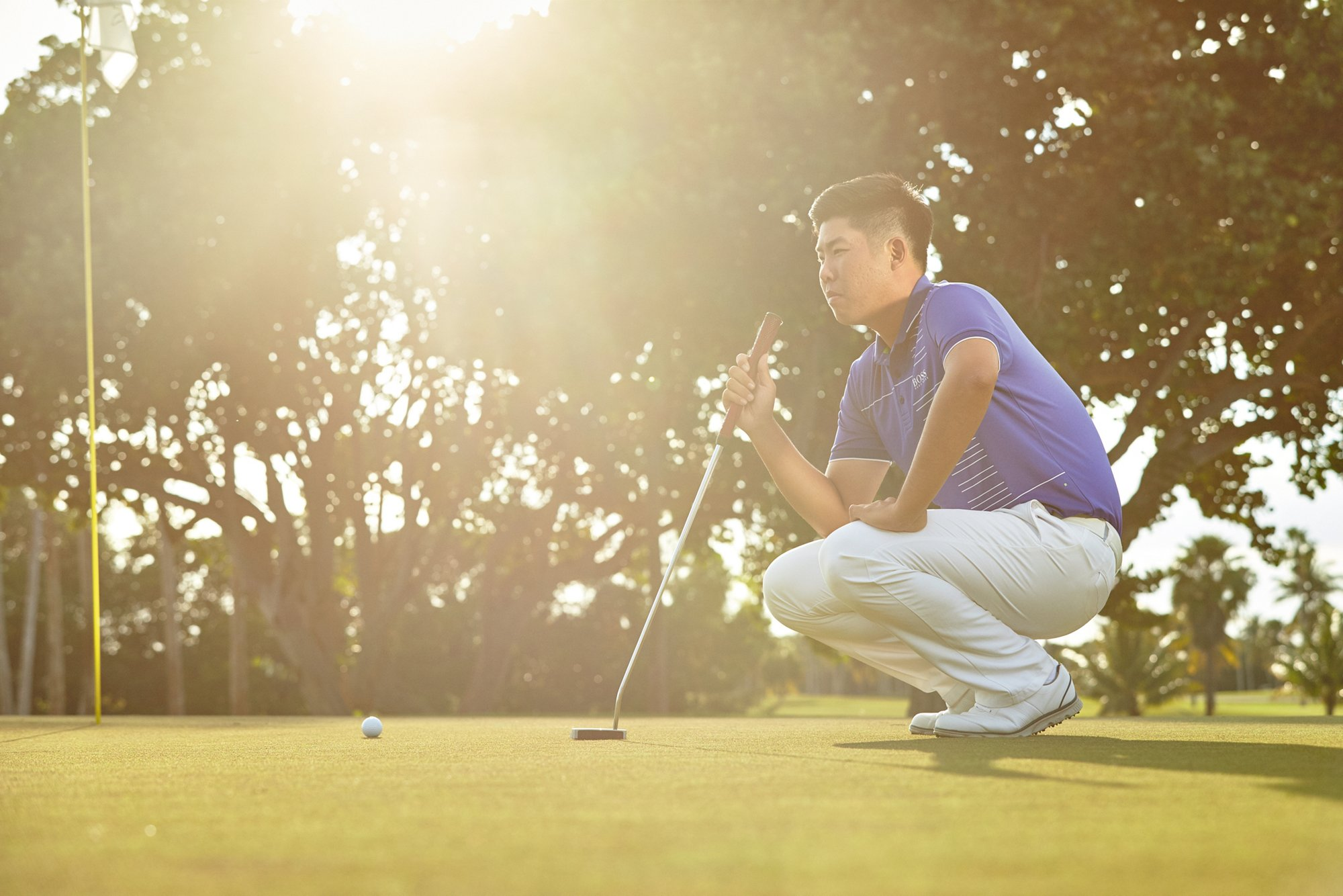 Byeong-Hun An wearing white pants and a blue polo shirt by BOSS Green