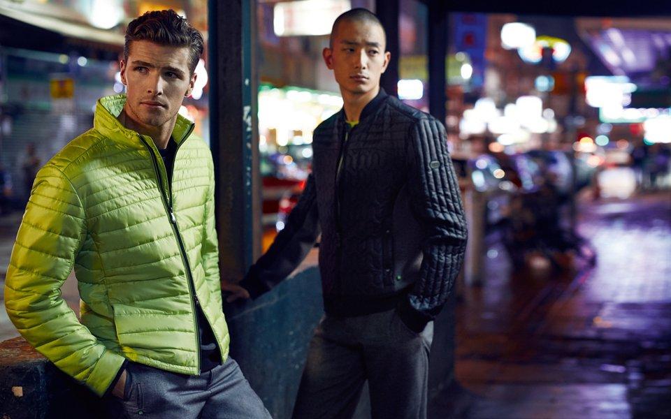 Mann in grüner Jacke und Hose von BOSS Green. Andere Männer in grauen Jacken von BOSS Green