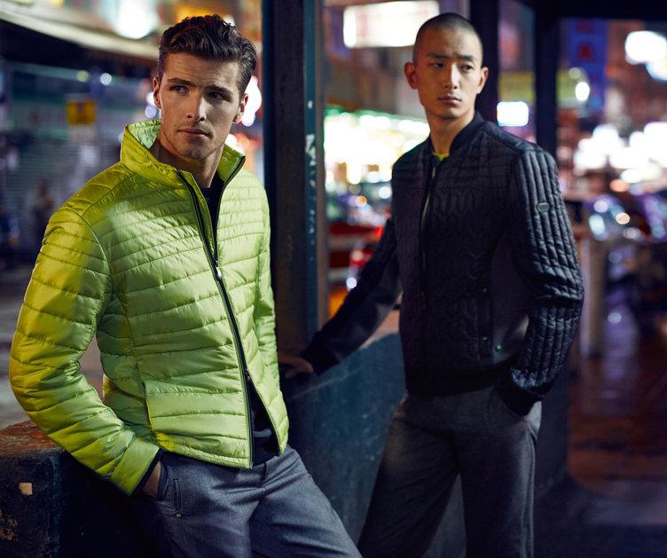 Un modèle porte un blouson et un pantalon verts BOSS Green. L'autre modèle porte un blouson gris BOSS Green