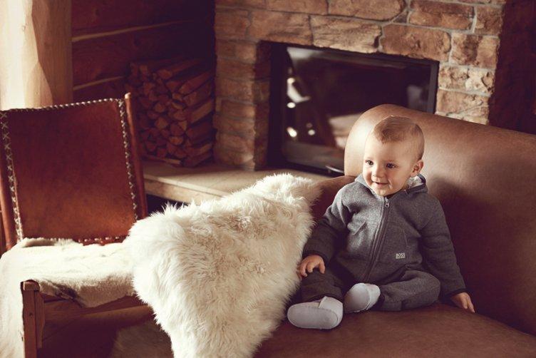 Baby met een grijs speelpakje van BOSS