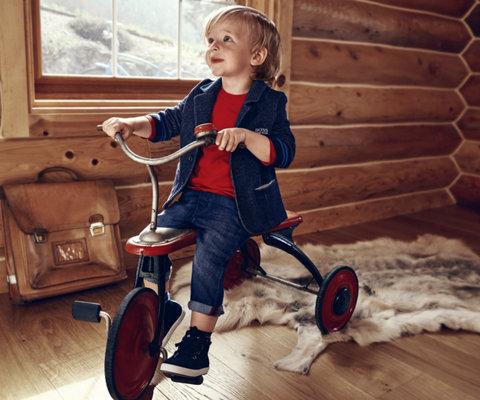 Peuterjongen met een blauwe jas, rode gebreide trui en schoenen van BOSS