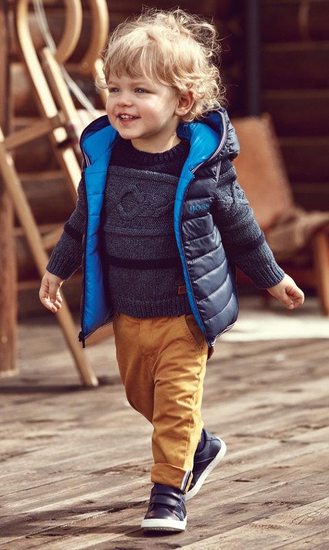 Peuterjongen met een blauwe jas, een blauw sweatshirt met dessin, een broek en blauwe schoenen van BOSS