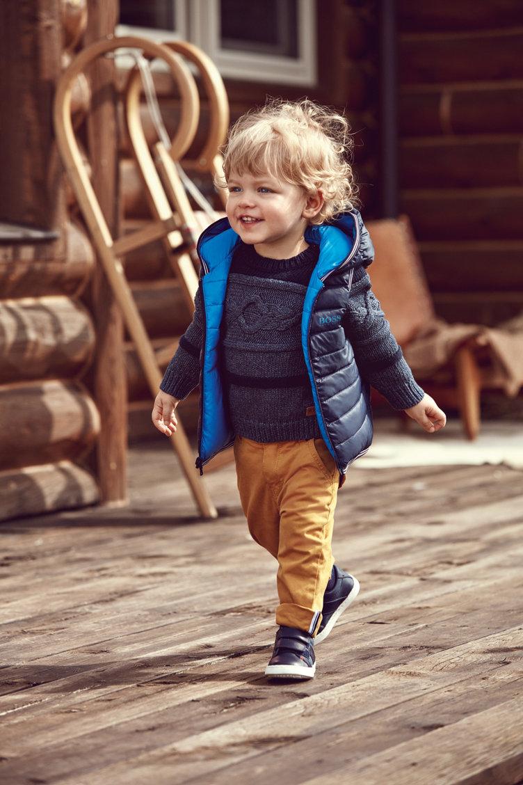 Petit garçon portant un blouson bleu, un sweat bleu à motif, un pantalon et des chaussures bleues BOSS