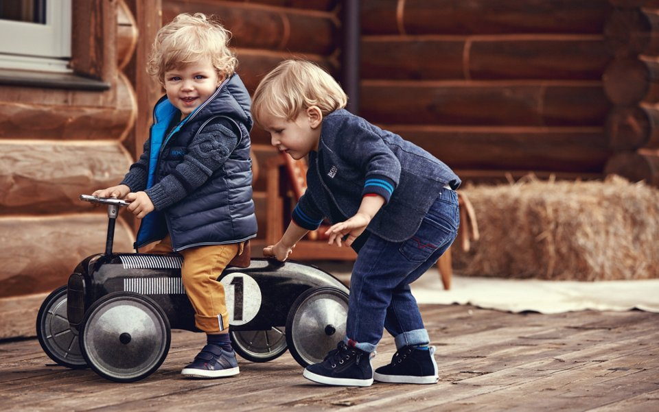 Toddlers wearing blue jackets, jeans and shoes by BOSS