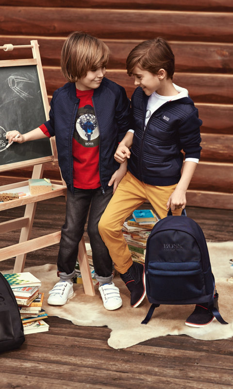 Boys waering blue jackets, red sweater, trousers and backpack by BOSS