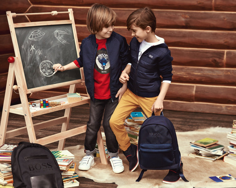 Jongens met blauwe jassen, rode trui, broek en rugzak van BOSS