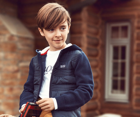 Jongen met een blauwe jas en een wit sweatshirt van BOSS