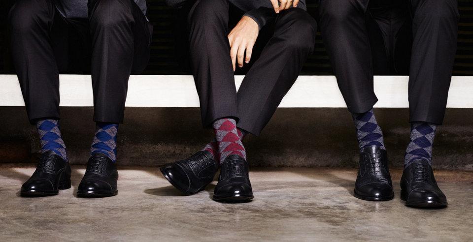 Model in blau-weiß gestreiften HUGO BOSS Socken. Kombiniert mit lässigem Outfit in Schwarz und Blau.