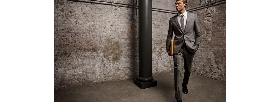 Grijs kostuum, wit overhemd, grijze broek met een stropdas, riem en schoenen van BOSS