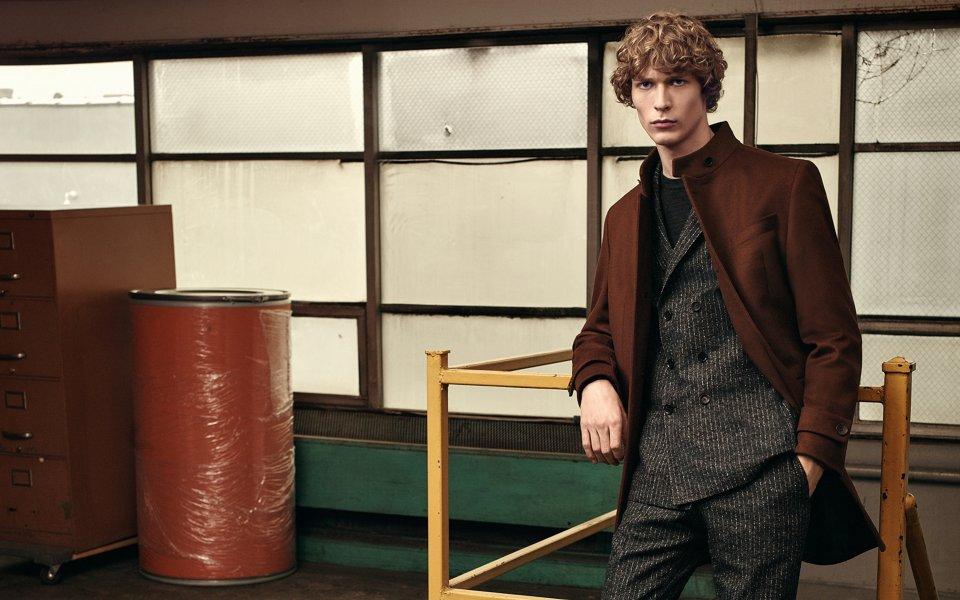 Brauner Mantel über einem schwarzem Anzug und schwarzem Strick mit braunen Schuhen von BOSS