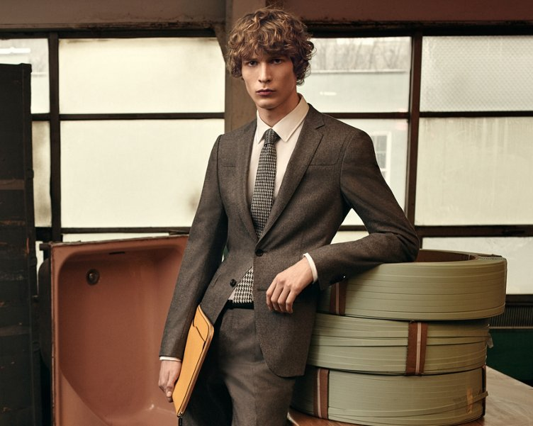 Grijze jas, wit overhemd, grijze broek met een grijs-witte stropdas, gele tas en witte sneakers van BOSS