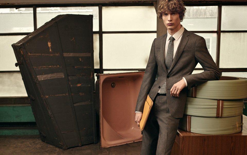 Graue Jacke, weißes Hemd, graue Hose, grau-weiße Krawatte, gelbe Tasche und weiße Sneaker von BOSS