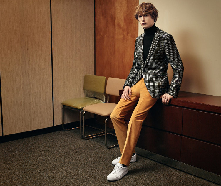 Grey jacket over black knitwear and yellow trousers with white sneakers and a black bag by BOSS