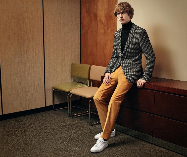 Graue Jacke über schwarzem Oberteil aus Strick, gelbe Hose, weiße Sneaker und schwarze Tasche von BOSS