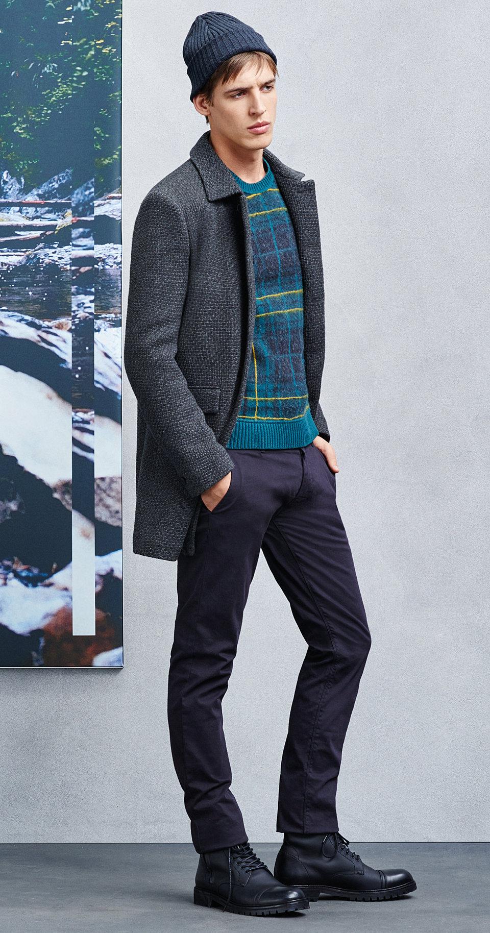 Blaue Mütze, graue Jacke, Pullover, schwarze Hose und schwarze Schuhe von BOSSOrange