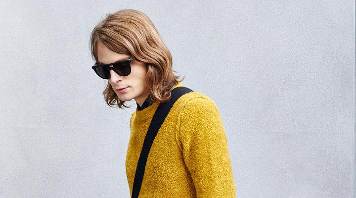 Gele gebreide trui over een zwart overhemd en zonnebril van BOSS Orange