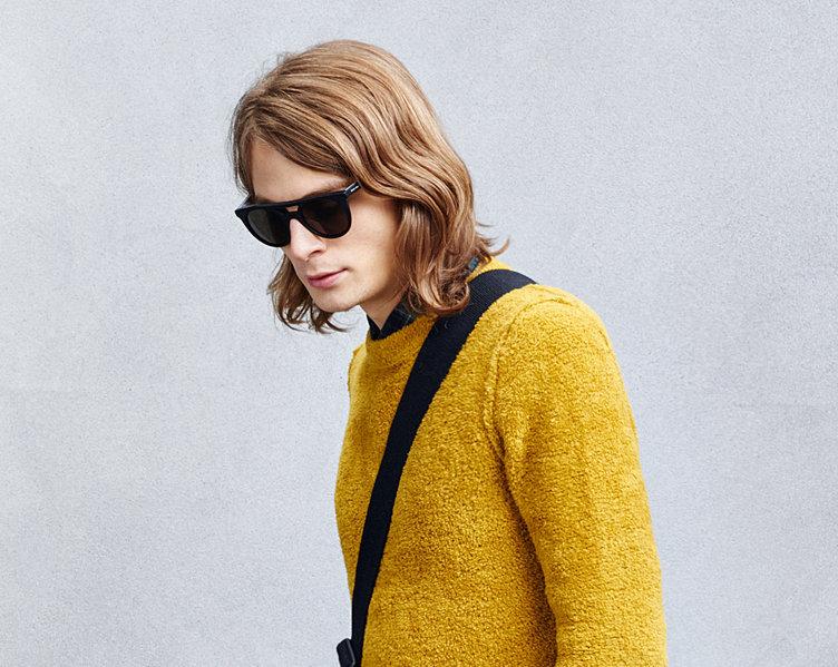 Gelber Strick über schwarzem Hemd und Sonnenbrille von BOSS Orange