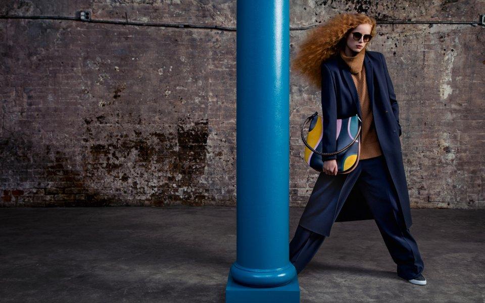 Robe bleue, haut en maille marron, pantalon bleu avec un sac à motif et des chaussures grises BOSS