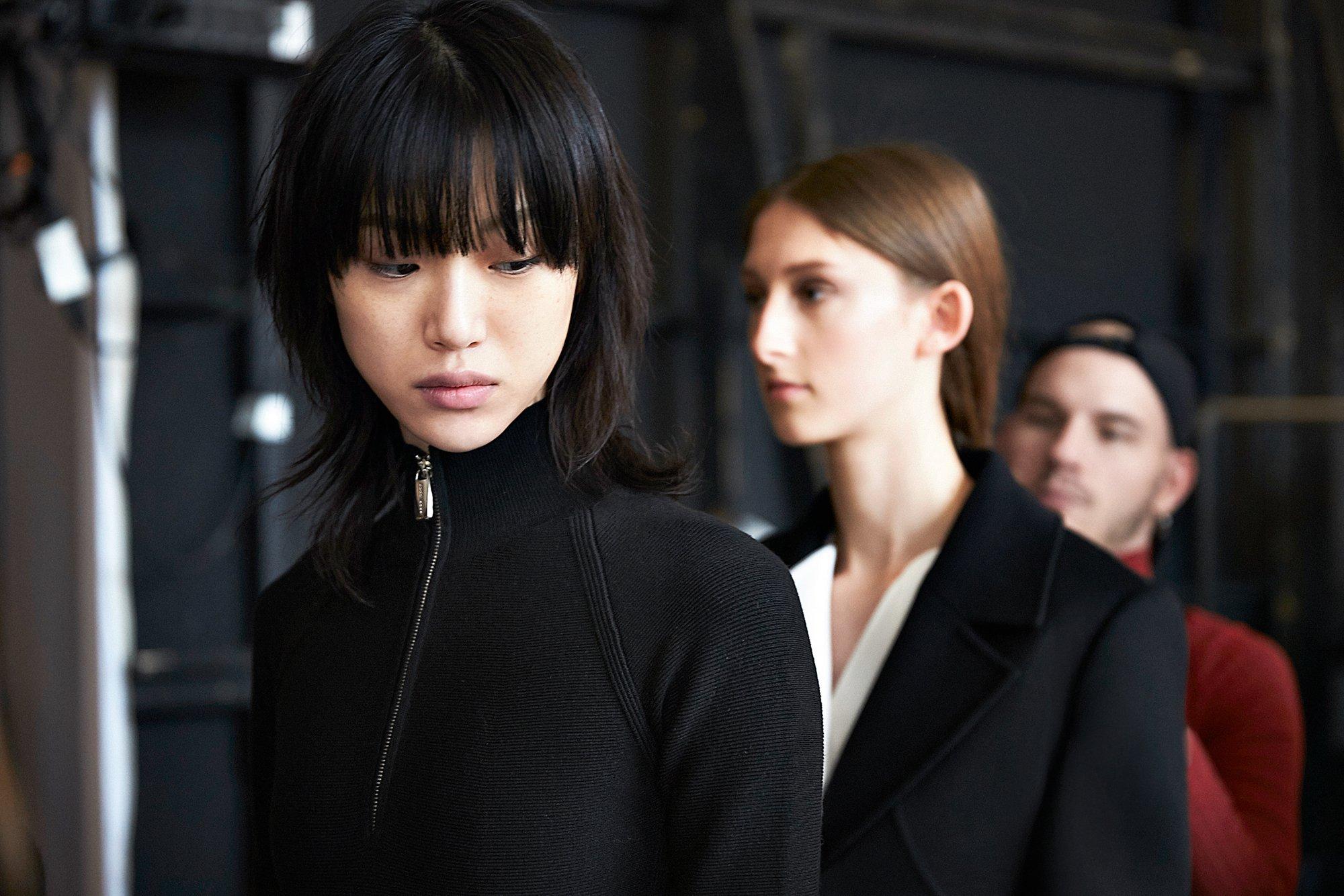 Mannequins en coulisse au défilé de la New York Fashion Week Automne/Hiver2016 portant une robe noire et un costume noir avec une chemise blanche BOSS