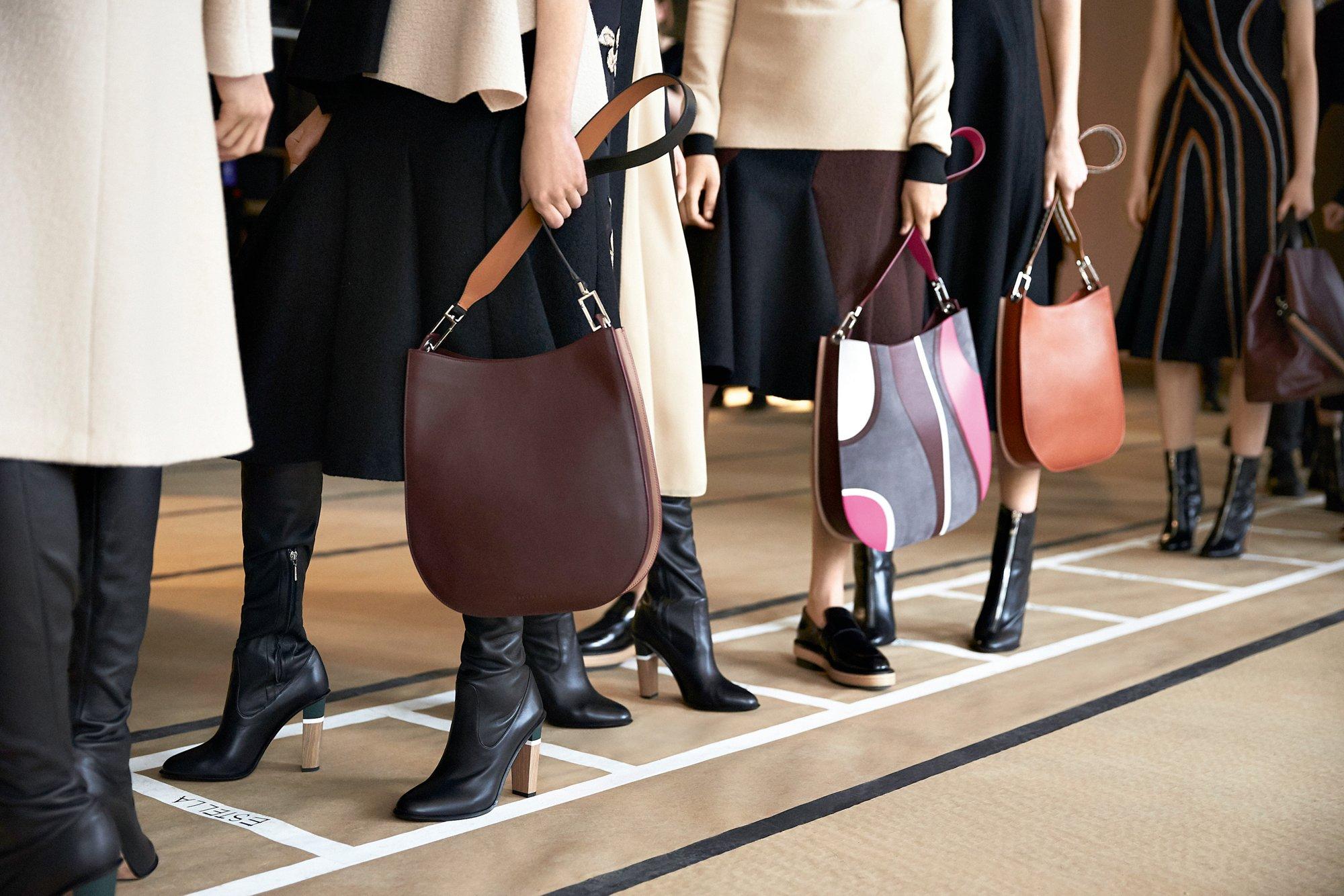 Mannequins en coulisse au défilé de la New York Fashion Week Automne/Hiver2016 portant le manteau orange, des robes noires et des chaussures BOSS