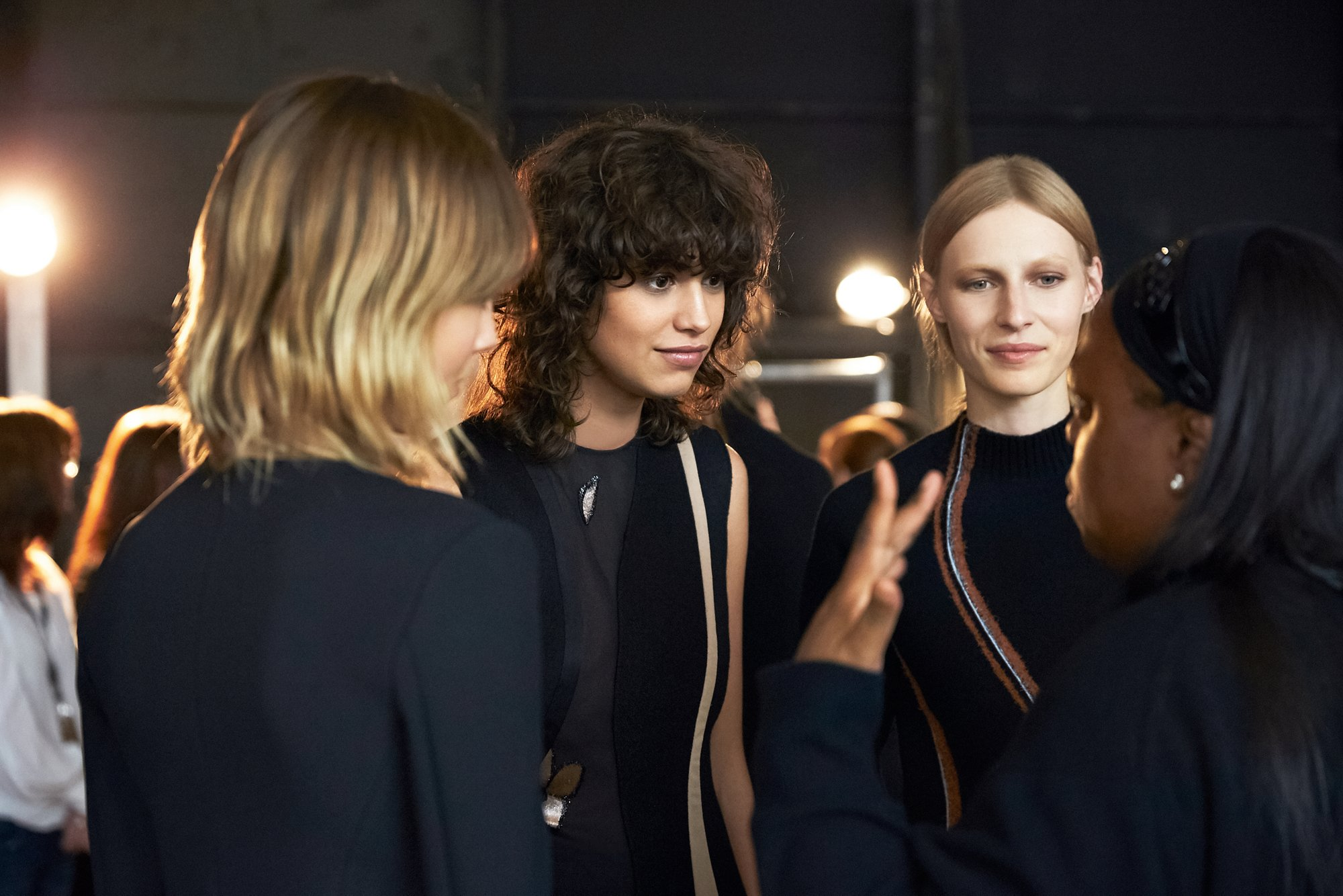 Modellen backstage tijdens de New York Fashion Week Herfst/Winter 2016, in zwarte en oranje jurken van BOSS