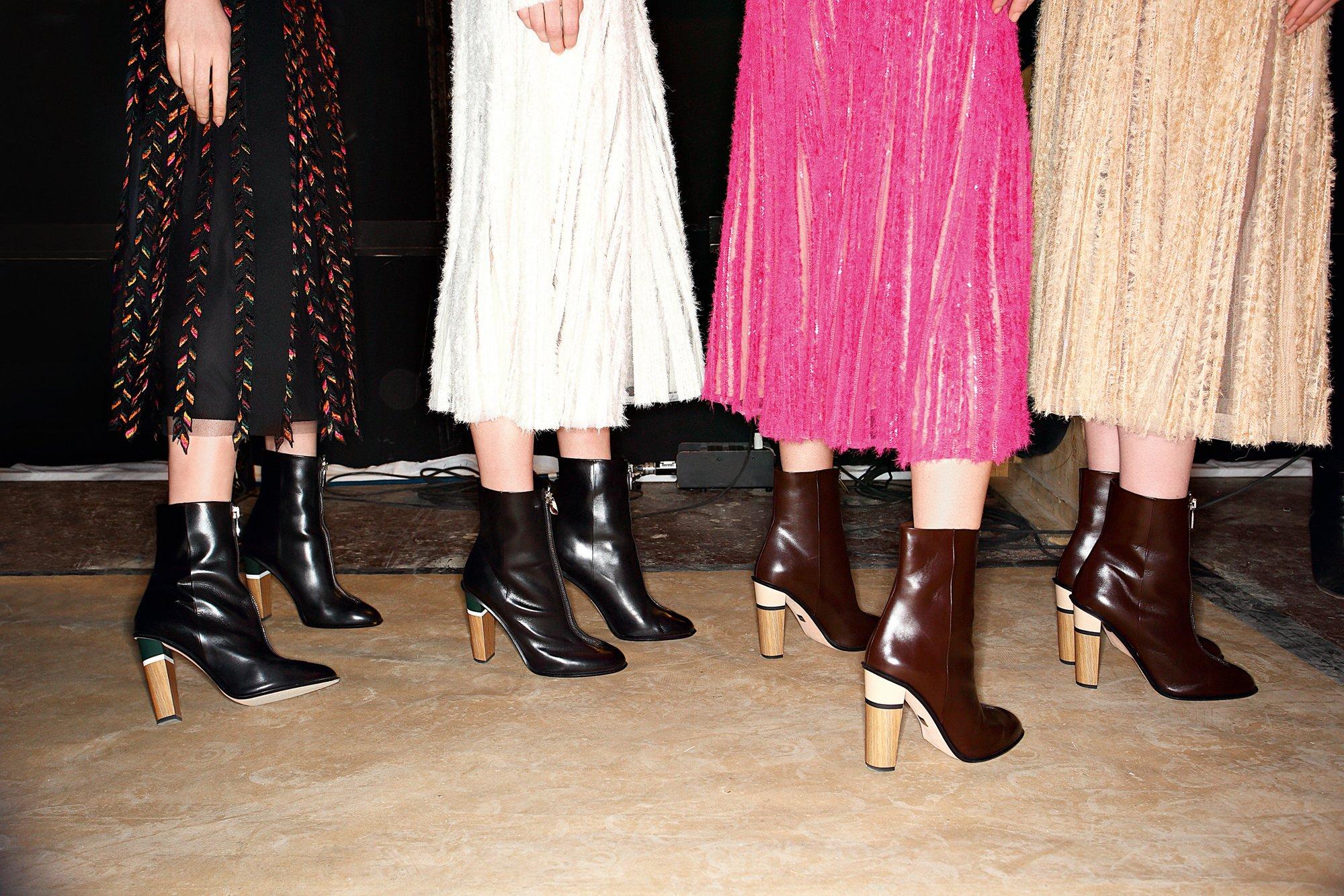 Jupes plissées noires, blanches, roses et beiges, bottes mi-hautes BOSS de couleur noire et marron