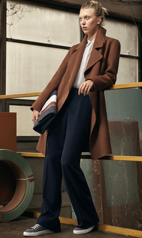 Manteau marron, chemisier blanc et pantalon bleu avec un sac gris BOSS