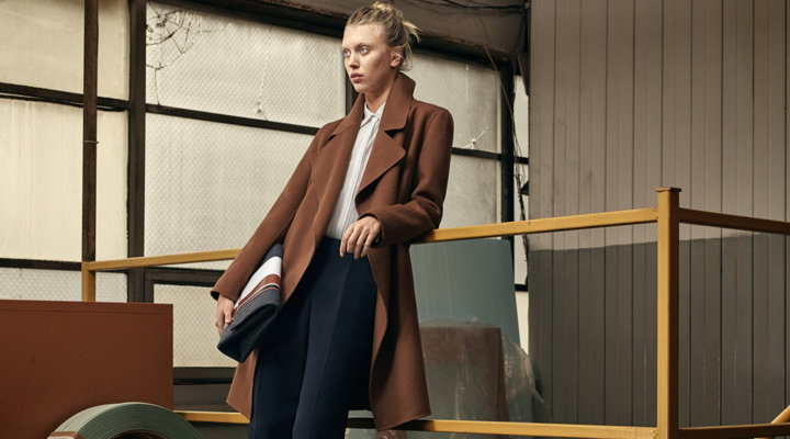 Brown coat over white blouse and blue trousers with a grey bag by BOSS