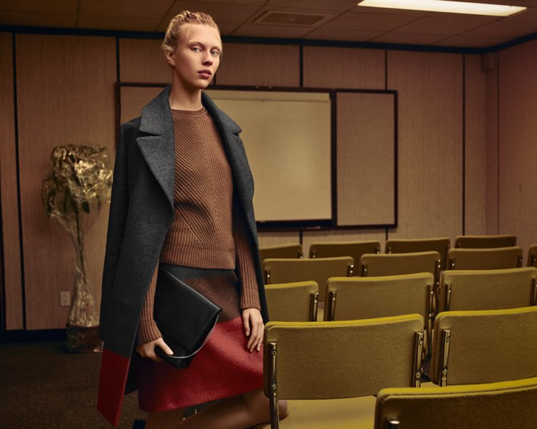 Grey coat over brown knitwear and red skirt with a blag leather bag by BOSS