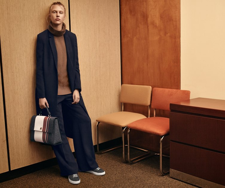 Dark blue coat with brown knitwear and dark blue trousers with a grey bag by BOSS