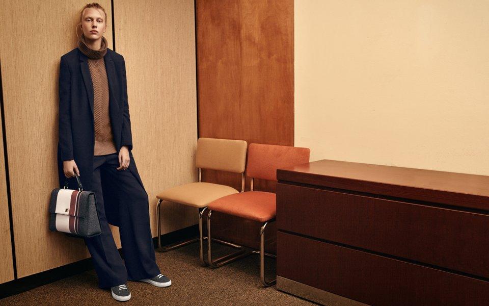 Dunkelblauer Mantel mit braunem Oberteil aus Strick, dunkelblaue Hose und graue Tasche von BOSS