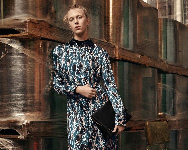 Blaues Kleid über schwarzem Strick mit schwarzen Schuhen und einer schwarzen Handtasche von BOSS