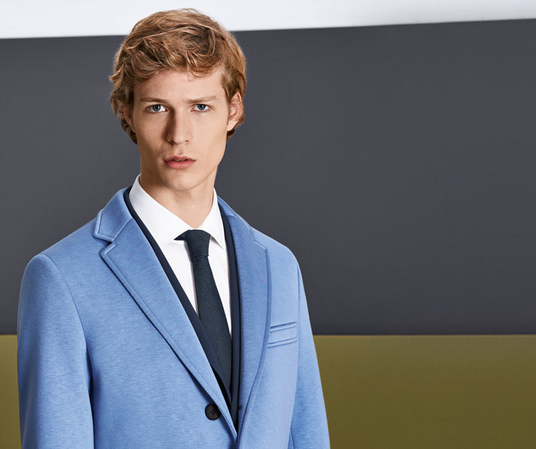 Model mit blau gemusterter HUGO BOSS Krawatte. Kombiniert mit blauem Anzug und weißem Hemd.