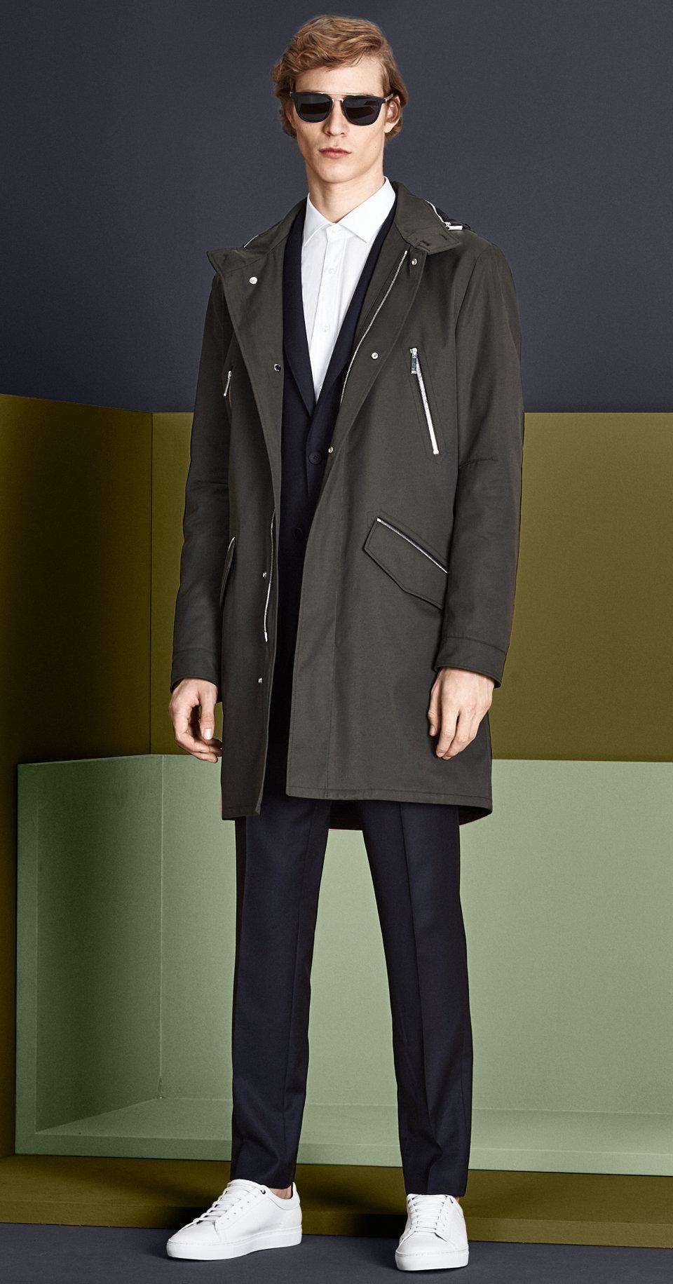 Khakifarbener Mantel, marineblauer Anzug, weißes Hemd, Sonnenbrille, dunkelblauer Gürtel und weiße Schuhe von BOSS