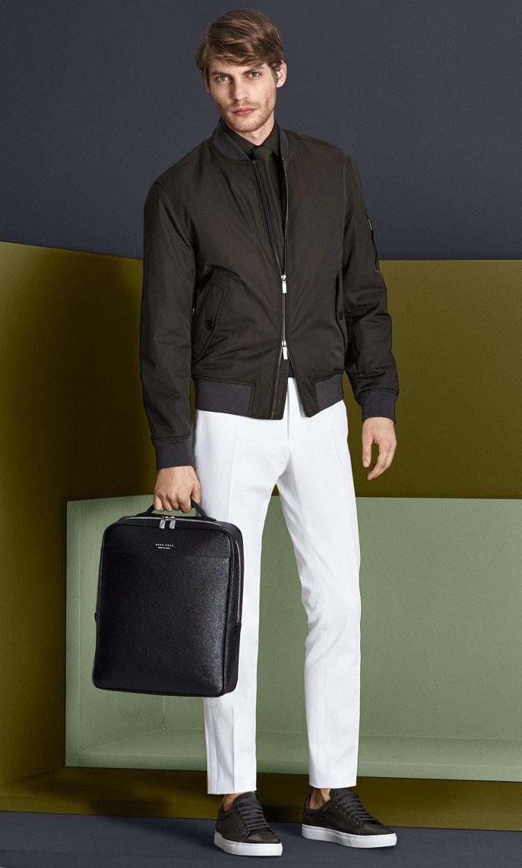 Khakifarbene Jacke, dunkelblaues Hemd, weiße Hose mit schwarzem Gürtel und Schuhen in Schwarz und Dunkelgrün von BOSS