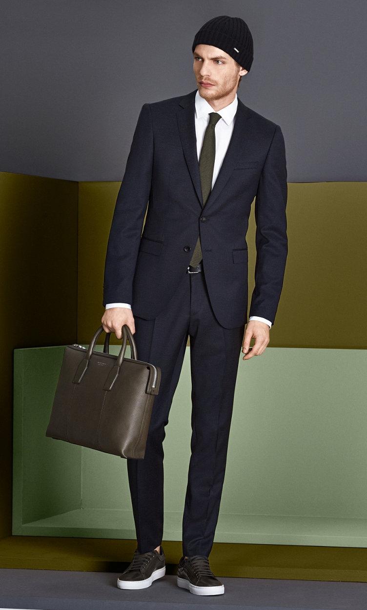 Dunkelblauer Anzug, weißes Hemd mit schwarzer Mütze, khakifarbener Krawatte, schwarzem Gürtel, khakifarbener Tasche und dunkelgrünen Schuhen von BOSS